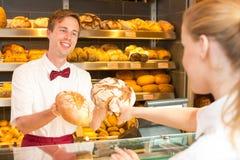 推销员在拿着面包的不同的类型面包店 免版税库存照片