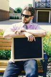 推销员坐长凳与做广告待售 与镇静面孔的商人与在背景的大厦 库存图片