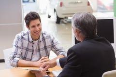 推销员显示客户在哪里签署成交 免版税库存照片