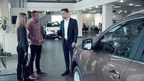 推销员谈话与在售车行里面的夫妇 库存图片