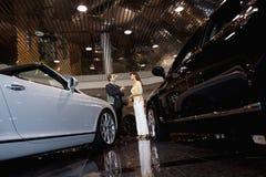 推销员谈话与妇女在汽车陈列室里 免版税图库摄影