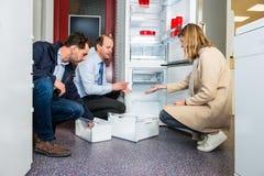 推销员给夫妇展示冰箱在超级市场 图库摄影