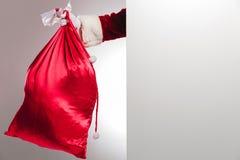 掩藏在一个空白的委员会后的圣诞老人 免版税库存照片