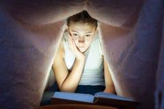 掩藏在一揽子和狂喜的阅读书下的年轻快乐的女孩 免版税库存照片