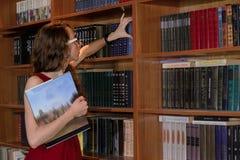 掩藏在书后的女大学生 免版税图库摄影