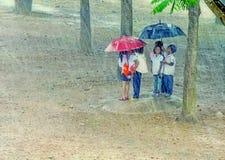 掩藏在伞下的孩子 免版税库存图片