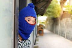 掩藏在入口后的夜贼在抢劫前 犯罪概念 免版税库存图片