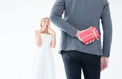 掩藏在后面后的新郎红色礼物盒为了使新娘在婚礼那天,妇女正面情感惊奇和面对吃惊的机会 免版税库存图片