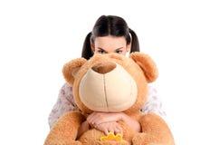 掩藏在大teddybear后的女孩。 免版税库存照片