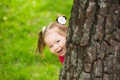 掩藏在巨大的树后的逗人喜爱的小女孩 库存照片