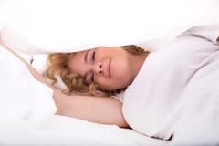 掩藏在床的少妇在板料下 免版税库存图片