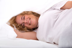 掩藏在床的少妇在板料下 库存照片