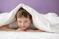 掩藏在床的微笑的男孩在一条白色毯子或床罩下 免版税库存照片