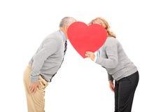 掩藏在心形的纸板后的成熟夫妇 免版税库存图片
