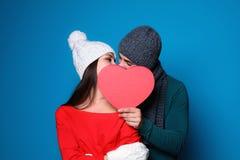 掩藏在心脏后的年轻夫妇,当亲吻在颜色背景时 庆祝庆祝圣诞节女儿帽子母亲圣诞老人佩带 免版税库存照片