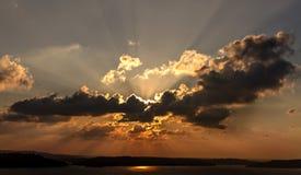 掩藏在日落之前的云彩后的太阳 图库摄影
