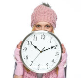 掩藏在时钟后的冬天帽子和围巾的少年女孩 免版税图库摄影