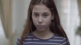 掩藏在有一张被绘的哀伤的面孔的蓝色气球后的画象俏丽的女孩对此然后把它放下 孩子是不快乐的 股票视频
