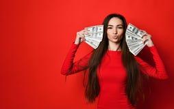 掩藏在束的红色礼服的年轻俏丽的妇女金钱钞票后 免版税库存照片