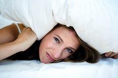 掩藏在枕头下的急切妇女 免版税库存照片