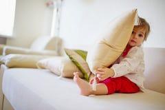 掩藏在枕头后的逗人喜爱的女孩 免版税库存图片