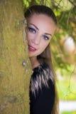 掩藏在树后的俏丽的女孩 免版税库存照片
