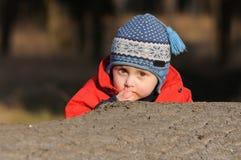 掩藏在树干后的男孩 免版税库存照片