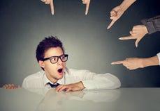 掩藏在桌下的害怕的人雇员被指责由把手指指向他的人 图库摄影
