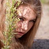 掩藏在植物后的白肤金发的妇女 免版税库存图片