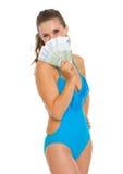 掩藏在欧元之后风扇的泳装的妇女  免版税图库摄影