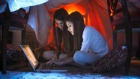 掩藏在毯子下和使用膝上型计算机的睡衣的两个逗人喜爱的女孩在晚上 图库摄影