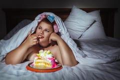 掩藏在毯子下和吃曲奇饼的美丽的少妇 免版税图库摄影