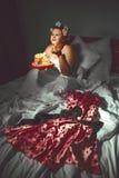 掩藏在毯子下和吃曲奇饼的美丽的少妇 免版税库存图片
