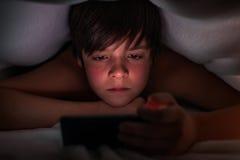 掩藏在毯子下和观看他的电话的年轻男孩 免版税库存照片