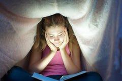 掩藏在毯子下和读嘘的年轻快乐的十几岁的女孩 免版税库存图片