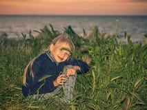掩藏在海滩的绿草的女孩在日落 库存照片