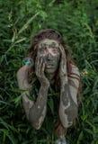 掩藏在灌木后的泥泞的亚马逊女孩在森林,当飞行在她附近时的肥皂泡 免版税库存图片