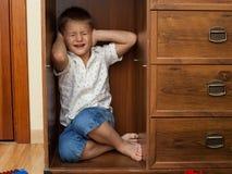 掩藏在碗柜和哭泣的小男孩 免版税库存照片