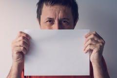 掩藏在空白的白皮书后的人 免版税库存照片