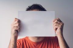掩藏在空白的白皮书后的人 库存图片