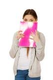 掩藏在笔记本后的青少年的妇女 库存照片
