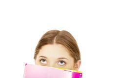 掩藏在笔记本后的青少年的妇女 免版税库存照片