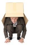 掩藏在箱子下的商人 库存照片