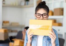 掩藏在箱子和神色后的一相当亚裔少女的画象 免版税库存图片