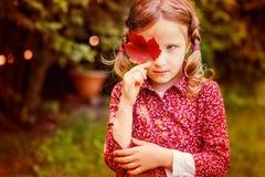 掩藏在红色秋天叶子后的逗人喜爱的哀伤的儿童女孩在庭院 免版税库存照片