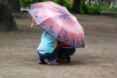 掩藏在腰臀部分的一把伞下的小男孩和女孩 免版税图库摄影