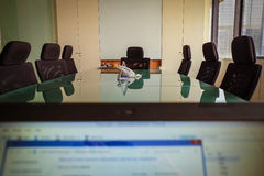 掩藏在膝上型计算机后的商人在会议第一perso 免版税库存图片