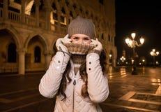 掩藏在衣领后的妇女,当花费乐趣时间在威尼斯时 免版税库存图片