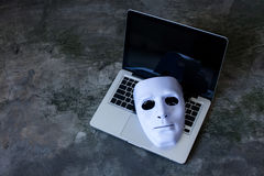 掩藏在计算机膝上型计算机的身分的匿名面具-互联网罪犯和网络安全威胁概念 免版税库存照片