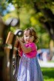 掩藏在长凳后的小女孩在公园 免版税图库摄影